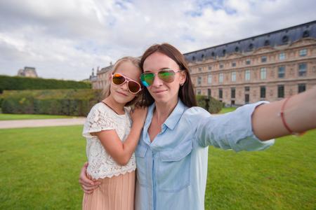 urban parenting: Happy mom and cute kid having fun together in Paris