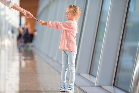 boarding: Adorable little girl at airport sitting on suitcase