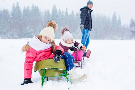 to go sledding: Young father rolls his little cute daughters on a sled in the snow outdoors Stock Photo
