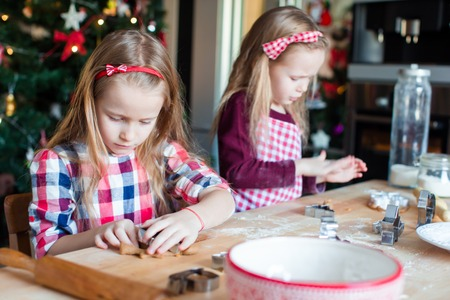 baking christmas cookies: Little girls decorating gingerbread house on Christmas