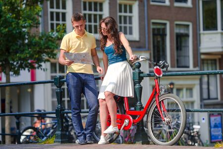 amsterdam: Young happy ouple on bikes in old streets in Amsterdam Stock Photo