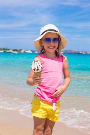 comiendo helado: Little adorable girl eating ice cream on tropical beach