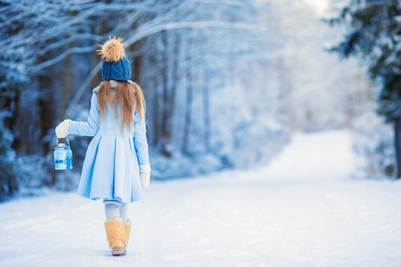 Cute little girl with flashlight having fun in winter day Banque d'images