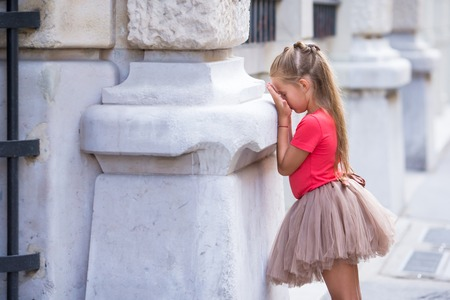 hide and seek: Little fashion girl playing hide and seek on street in Paris outdoors