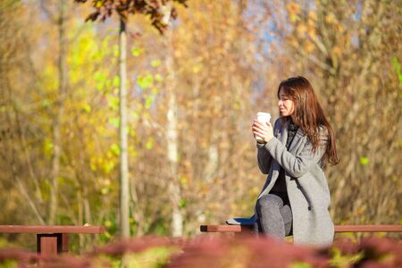 Fall concept - beautiful girl drinking coffee in autumn park  under fall foliage Stock Photo
