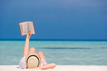 Young woman is reading a book lying on tropical white beach