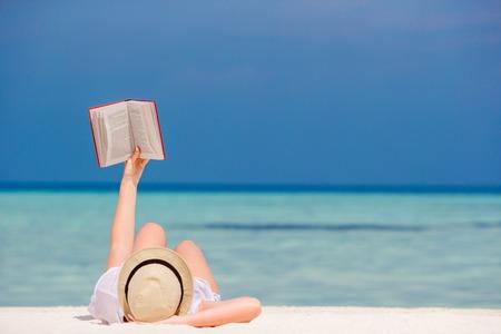 젊은 여자는 열 대 하얀 해변에 누워 책을 읽고