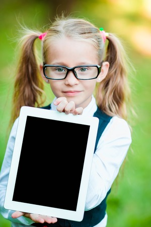 Happy little girl holding tablet PC outdoors in park on beautiful sunny day