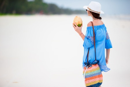woman beach: Happy young woman drinking coconut milk on beach