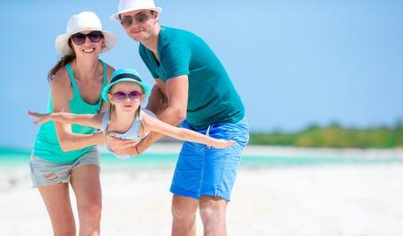 Happy family of three enjoying beach vacation