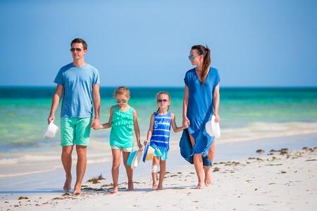 family holidays: Happy beautiful family on white beach having fun