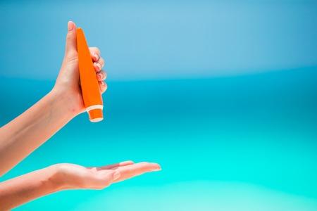 Femme mains mettre un écran solaire à partir d'une bouteille suncream fond de la mer