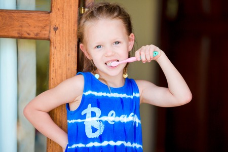 dentalcare: Little girl brushing her teeth in bathroom Stock Photo