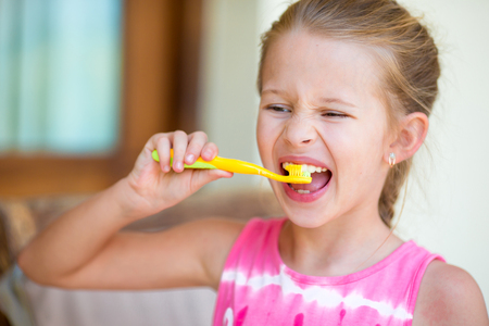 hygeine: Little girl brushing her teeth in bathroom Stock Photo