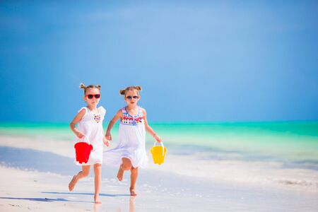 kids playing beach: Adorable little sisters at beach during summer vacation