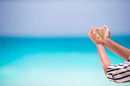 consent: Woman hands holding white tropical beach form heart shape