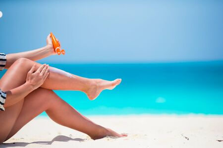 suncare: Young woman apply cream on her nose at beach