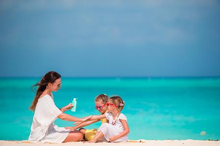 그녀의 아이들에 태양 크림을 적용하는 젊은 어머니