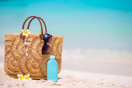 a straw: Beach accessories - bag, straw hat, sunglasses on white beach Stock Photo