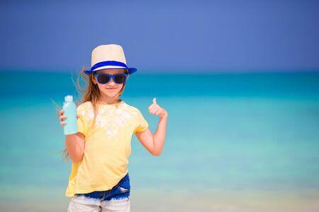 lotion bottle: Little adorable girl in swimsuit holds suntan lotion bottle