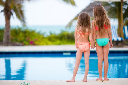 Adorable little girls playing in outdoor swimming pool Stock Photo