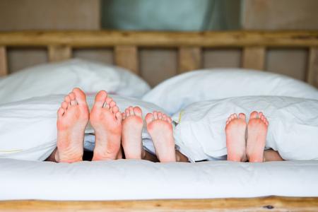 Pies de una familia en la cama - padre y dos niños