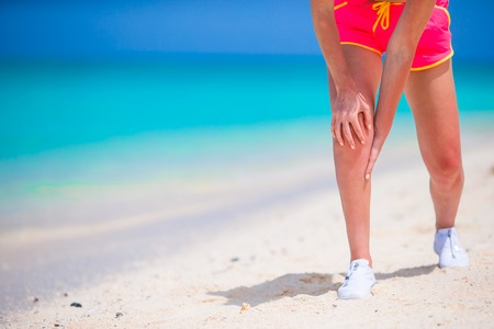 excruciating: Female Athlete Suffering From Pain In Leg While Exercising Stock Photo