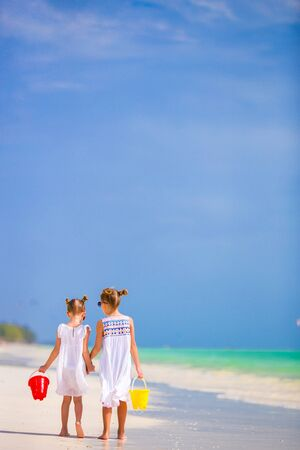youngbaby: Little adorable girls with eggs on tropical beach Stock Photo