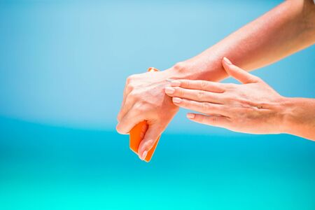 suncream: Woman hands putting sunscreen from a suncream bottle background the sea