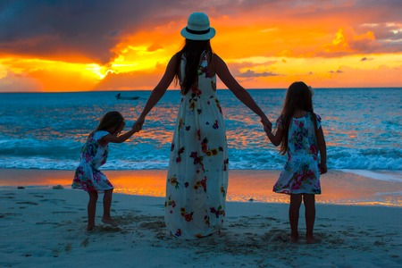 adult hand: Little girls and her mother having fun at sunset on the island Stock Photo