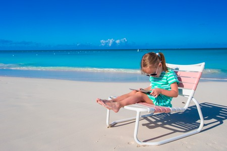 girl laptop: Little girl with laptop on beach during summer vacation