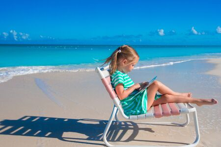 little girl beach: Little girl with laptop on beach during summer vacation