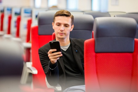 treno espresso: Tourist writes a message on his phone while traveling by express train Archivio Fotografico