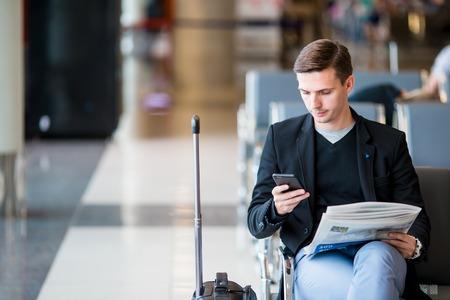 Man passenger in an airport lounge waiting for flight aircraft