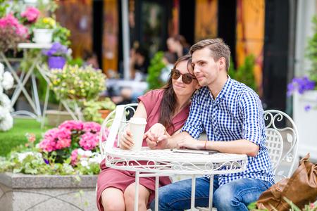 Glückliches Paar, welches das Sitzen im Café im Freien genießt Standard-Bild