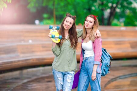 Two hipster cute girls with skate outdoors Stock Photo