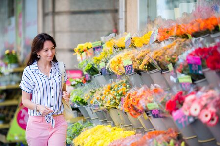 sale shop: Beautiful young girl selecting flowers at flower market Stock Photo