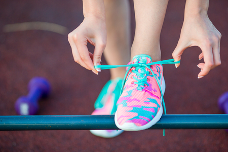 lacing sneakers: Weight loss - runner tying laces. Woman getting ready for jogging workout. Closeup of running shoes.