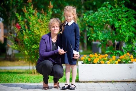 Grandmother brings her little granddaughter to school.
