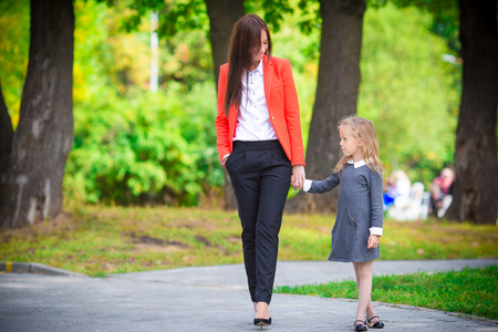 brings: Mother brings her little daughter to school. Stock Photo
