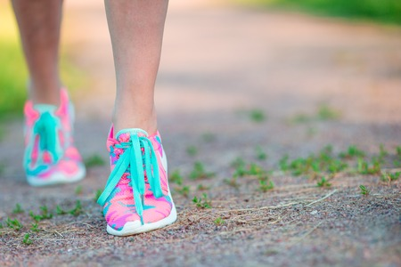 Weight loss - runner tying laces. Woman getting ready for jogging workout. Closeup of running shoes.