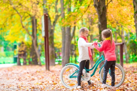 back alley: Adorable girl riding a bike at beautiful autumn day Stock Photo