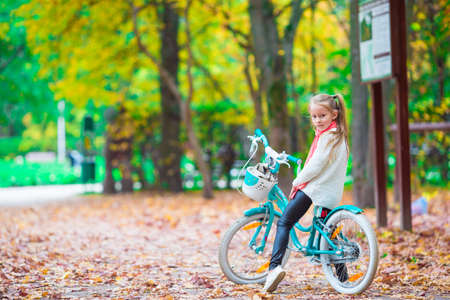 back alley: Adorable girl riding a bike on beautiful autumn day