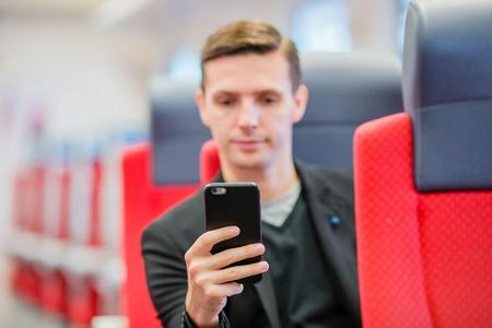 treno espresso: scrive Tourist un messaggio sul suo telefono mentre viaggia in treno Archivio Fotografico