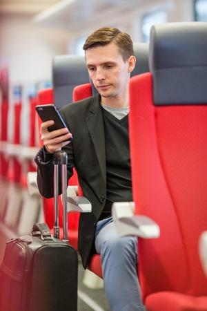 treno espresso: Tourist writes a message on his phone while traveling by express train Archivio Fotografico