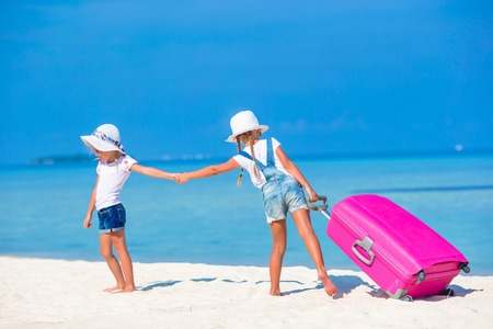 portmanteau: Little adorable girls with big colorful suitcase in hands walking on tropical beach Stock Photo