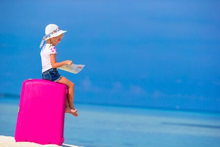 portmanteau: Little cute girls with big suitcase and a map on tropical beach