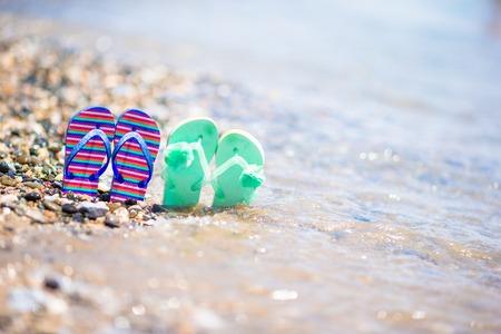 flops: Kids flip flops on beach in front of the blue sea