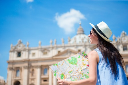 Happy young woman with a city map in Vatican city and St. Peters Basilica church, Rome, Italy Stock Photo