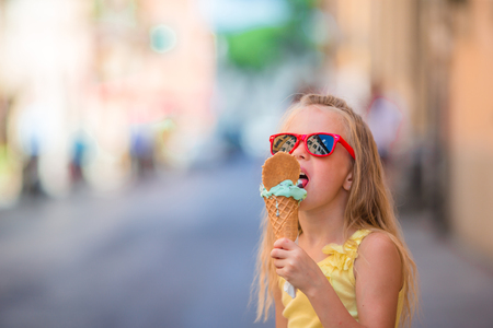 Adorable little girl eating ice-cream outdoors at summer Stock Photo